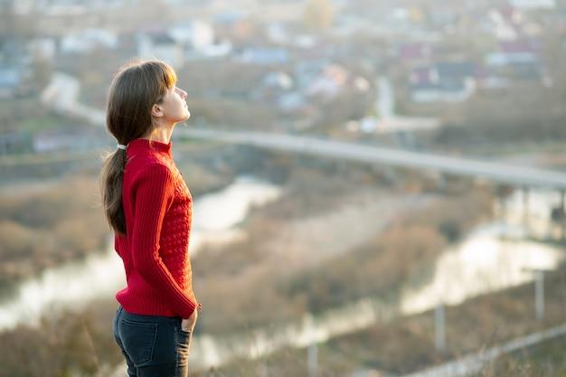 Mujer joven en la chaqueta roja que se coloca al aire libre que disfruta de visión de la tarde. concepto de relajación, libertad y bienestar.