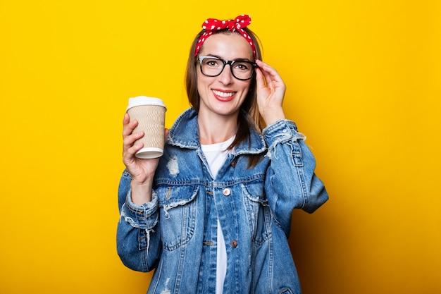 Mujer joven en chaqueta vaquera, diadema y gafas sosteniendo vaso de papel