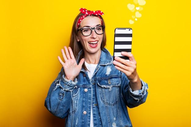 Mujer joven con chaqueta vaquera y gafas sostiene un teléfono en sus manos y habla por video chat en una pared amarilla.