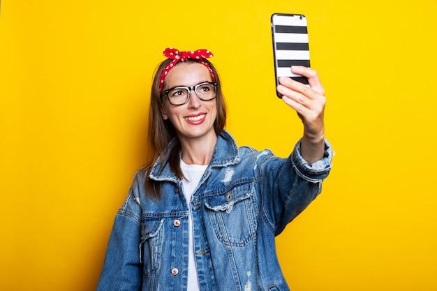 Mujer joven en una chaqueta vaquera y gafas sostiene un teléfono