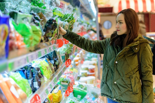 Una mujer joven con una chaqueta verde elige verduras en los estantes de los supermercados.