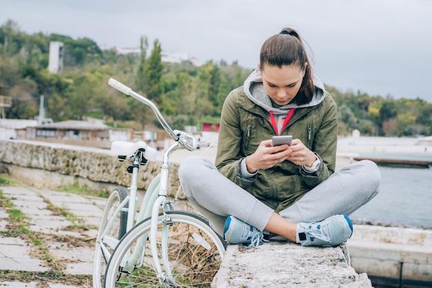 Mujer joven en una chaqueta verde usando un teléfono móvil