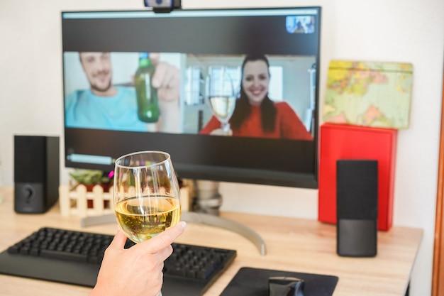 Mujer joven chateando y bebiendo vino en reunión de computadora con amigos
