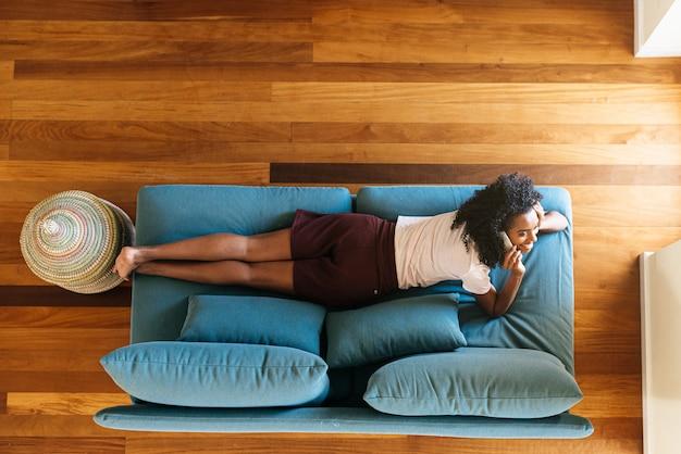 Mujer joven chateando en el teléfono inteligente acostado en el sofá en casa