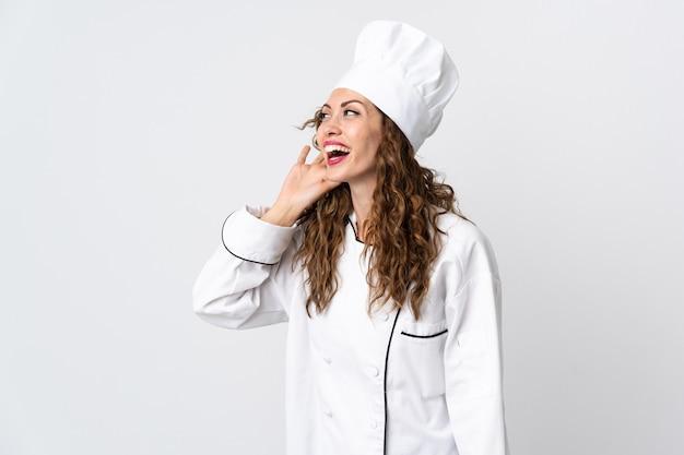Mujer joven chef aislada en la pared blanca escuchando algo poniendo la mano en la oreja