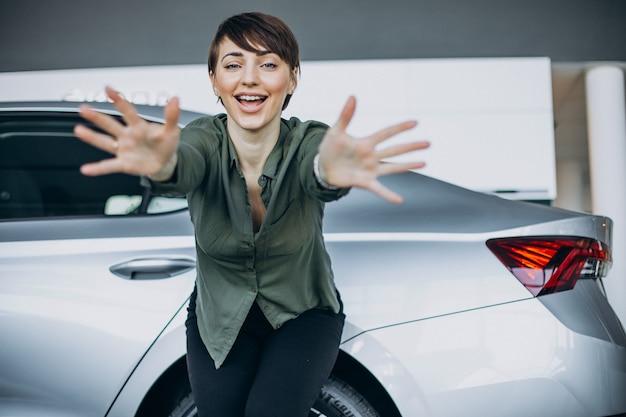 Mujer joven choosimng un coche en una sala de exposición de coches