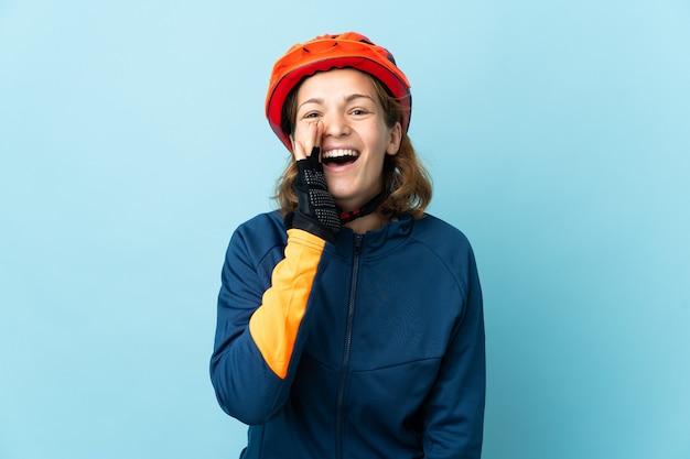 Mujer joven ciclista aislada en la pared azul gritando con la boca abierta