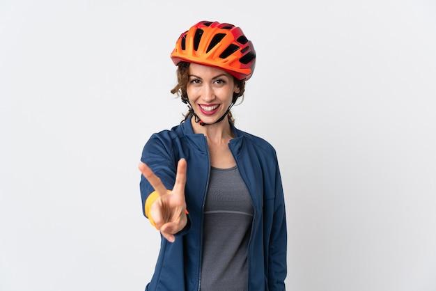 Mujer joven ciclista aislada en la pared blanca sonriendo y mostrando el signo de la victoria
