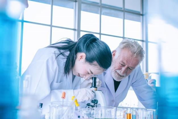Mujer joven científico y médico con microscopio en laboratorio