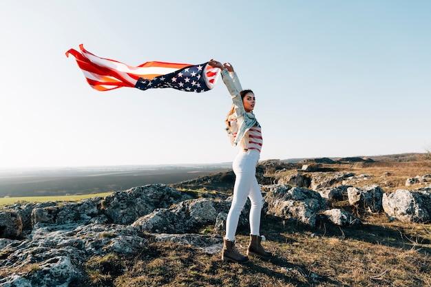 Mujer joven en la cima de la montaña con bandera estadounidense ondeando