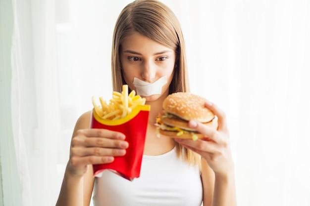 Mujer joven con cinta adhesiva sobre la boca, impidiéndole comer comida chatarra.