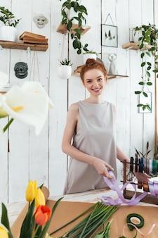 Mujer joven con cinta entre flores y sonriente