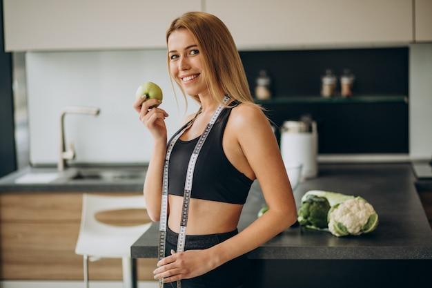 Mujer joven con cinta métrica en la cocina