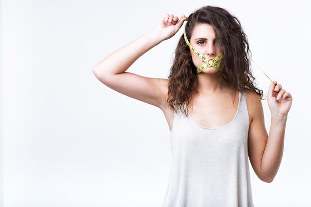 Mujer joven con la cinta métrica que cubre la boca aislada en el fondo blanco.