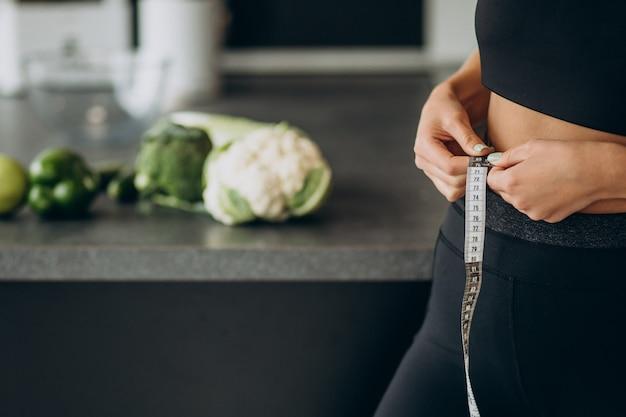 Mujer joven con cinta métrica en weist en la cocina