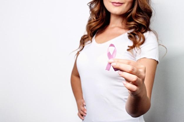 Mujer joven con una cinta rosa que apoya la concienciación sobre el cáncer de mama