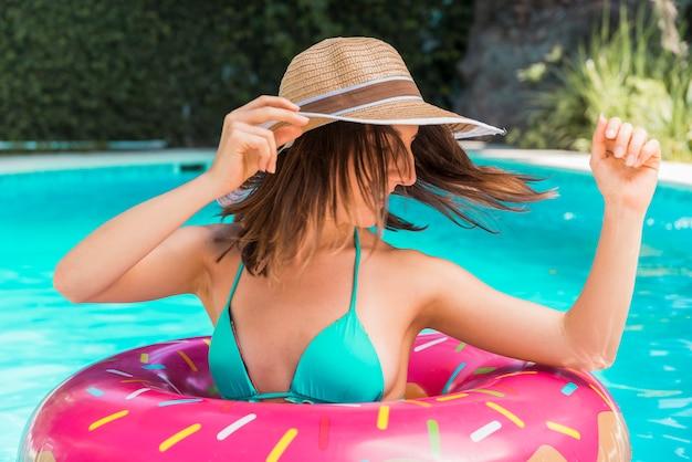 Mujer joven con círculo de piscina en piscina