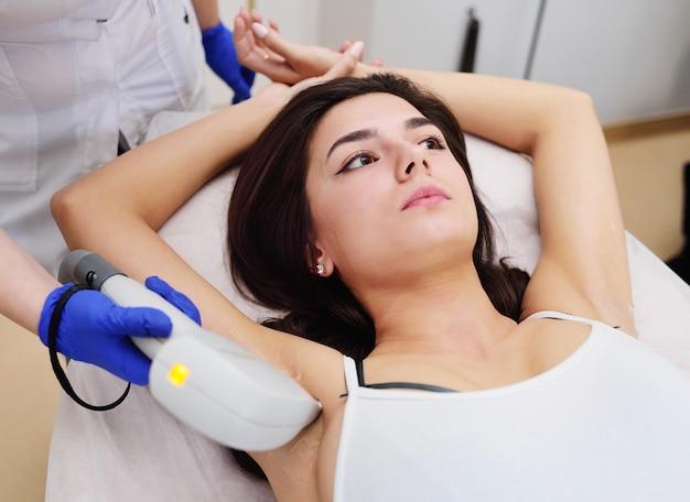 Una mujer joven en una clínica de cosmetología moderna.