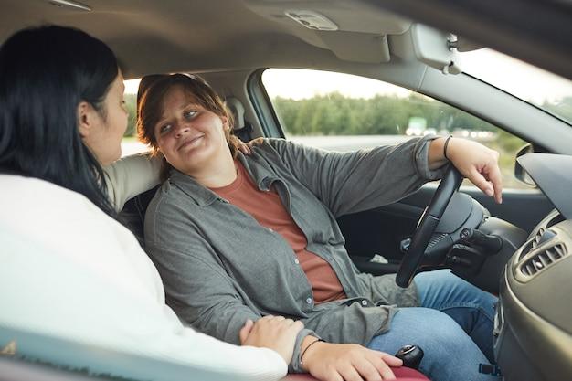 Mujer joven en coche hablando con su novia durante su viaje