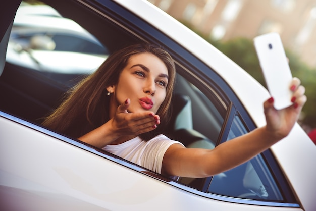 Mujer joven en el coche que va de vacaciones como pasajero hace selfie.