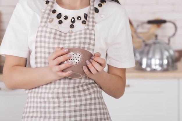Mujer joven en la cocina. ama de casa de pie en la cocina. cocina femenina.