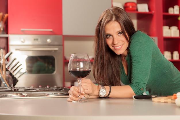Mujer joven en la cocina con una copa de vino tinto