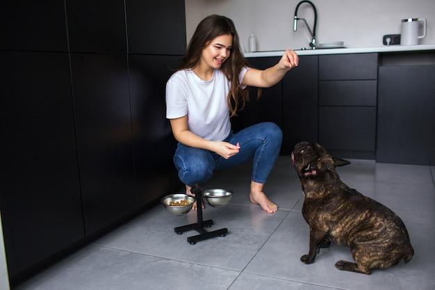 Mujer joven en la cocina durante la cuarentena. chica sentarse y jugar con bulldog francés. entrenar a la mascota para que haga comandos y coma comida para perros después de eso