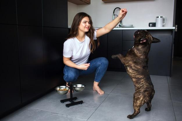 Mujer joven en la cocina durante la cuarentena. chica traning bulldog francés con comida para perros y jugando con mascotas. perro de piel oscura saltar.