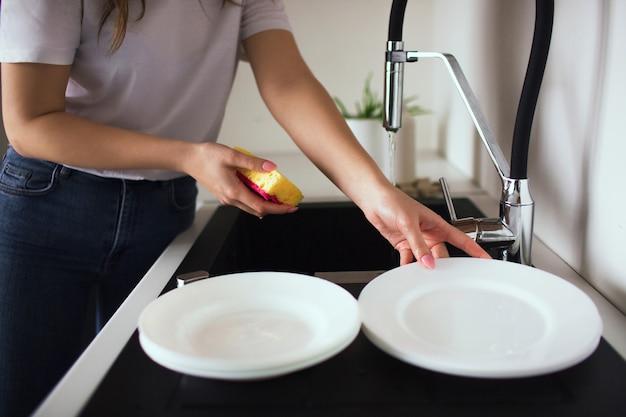 Mujer joven en la cocina durante la cuarentena. corte la vista de las manos de la niña sosteniendo una esponja con lavavajillas y tome un plato blanco. lavar los platos en el fregadero.