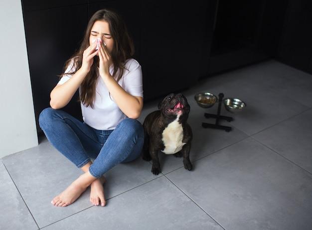 Mujer joven en la cocina durante la cuarentena. siéntate en el piso y estornuda en un pañuelo blanco. niña enferma y enferma con síntomas de coronavirus. el bulldog de piel oscura se sienta además y mira hacia arriba.