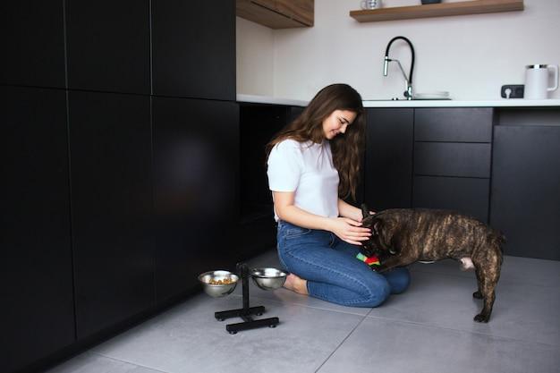 Mujer joven en la cocina durante la cuarentena. siéntate en el piso y juega con el bulldog francés de piel oscura. use un juguete de pelota suave para pasar tiempo lúdico con la mascota.