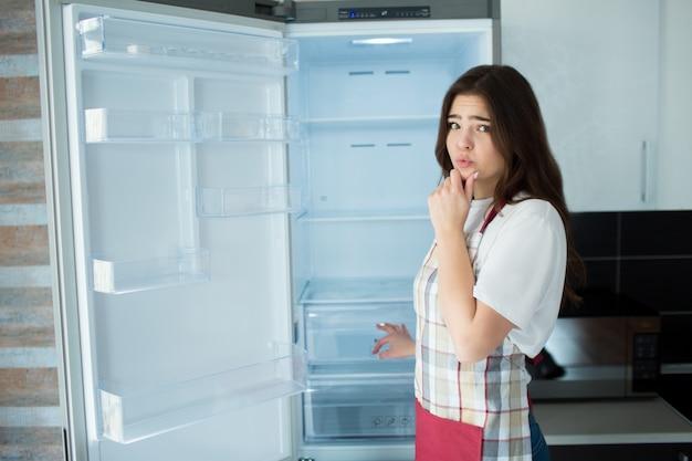 Mujer joven en la cocina. párese frente al refrigerador abierto. no hay comida o comida en los estantes para cocinar.