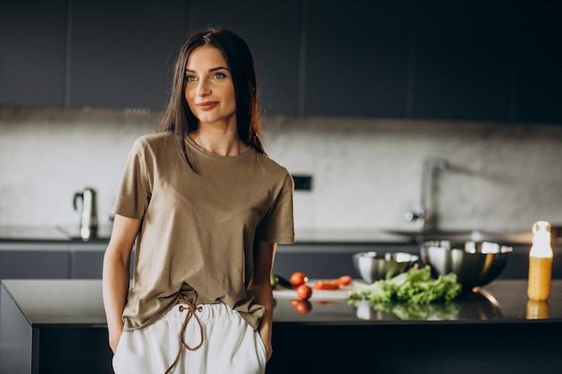 Mujer joven en la cocina preparándose para la cena