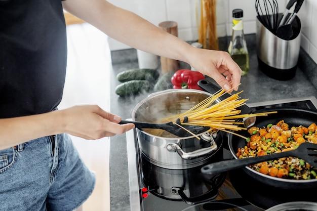 Mujer joven cocinando pasta de espagueti fresco en casa con verduras.