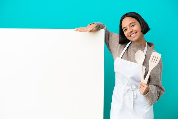 Mujer joven cocinera de raza mixta con un gran cartel aislado sobre fondo azul con expresión facial sorprendida