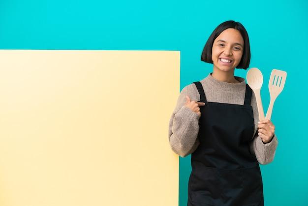 Mujer joven cocinera de raza mixta con un gran cartel aislado sobre fondo azul con expresión facial sorpresa