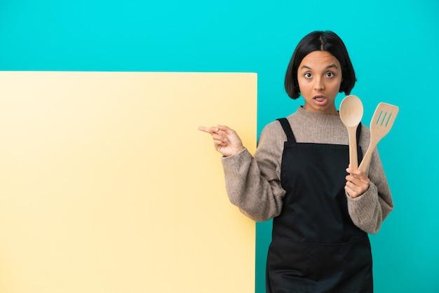 Mujer joven cocinera de raza mixta con un gran cartel aislado sobre fondo azul con expresión de sorpresa mientras apunta hacia el lado
