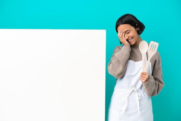 Mujer joven cocinera de raza mixta con un gran cartel aislado sobre fondo azul sonriendo mucho