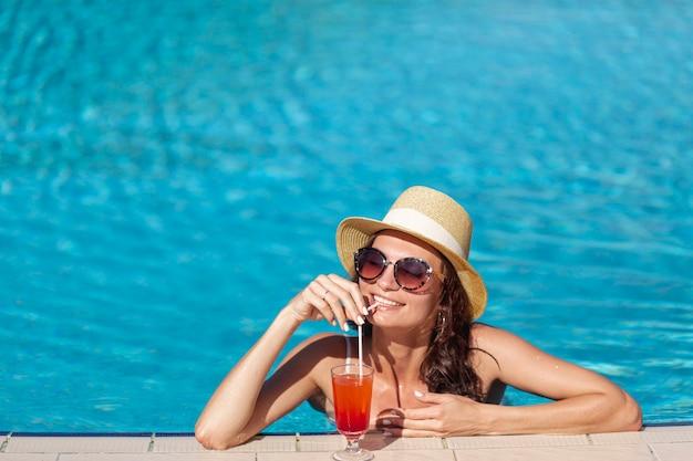 Mujer joven con un cóctel sentado en una piscina