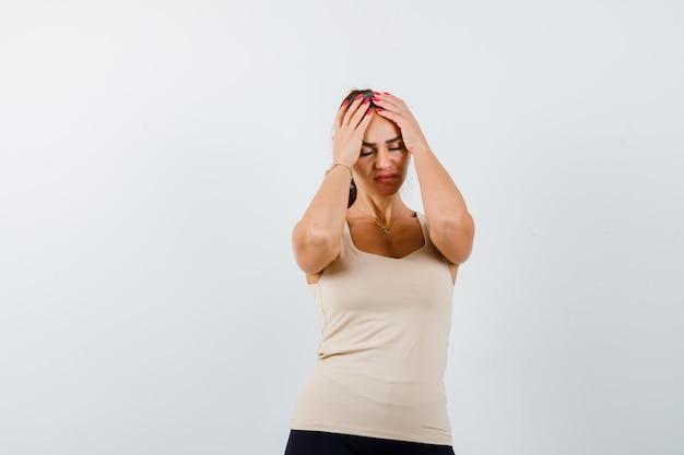 Mujer joven cogidos de la mano en la cabeza en camiseta sin mangas beige y mirando exhausto. vista frontal.