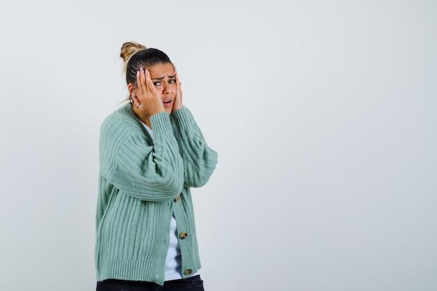 Mujer joven cogidos de la mano a las mejillas en camiseta blanca y chaqueta de punto verde menta y mirando emocionado
