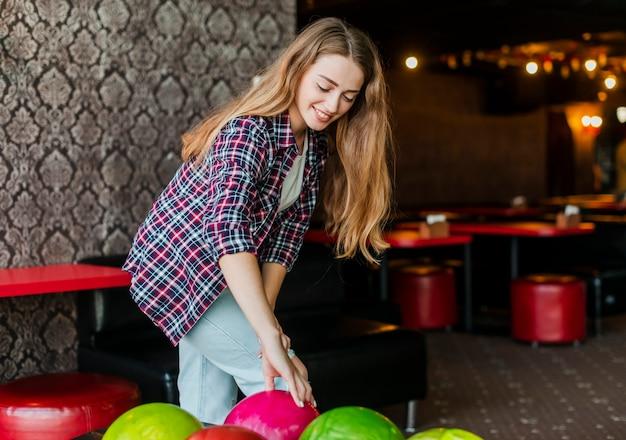 Mujer joven con coloridas bolas de boliche