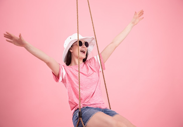 Mujer joven en un columpio sobre un fondo rosa.