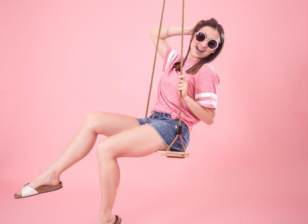 Mujer joven en un columpio sobre una superficie rosa