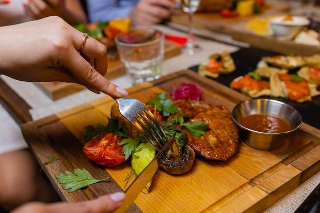 Mujer joven comiendo bistec a la parrilla en restaurante.