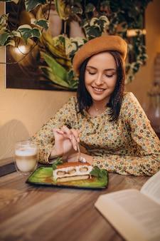 Mujer joven comiendo delicioso tiramisú en un café