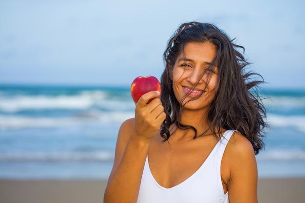 Mujer joven comiendo fruta en la playa