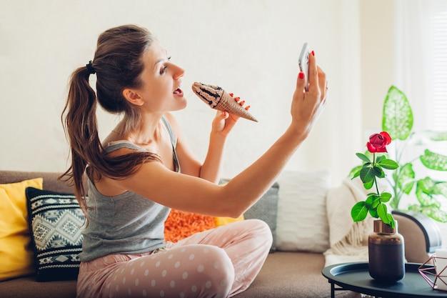 Mujer joven comiendo helado de chocolate en cono sentado en el sofá en casa y tomando selfie con smartphone.