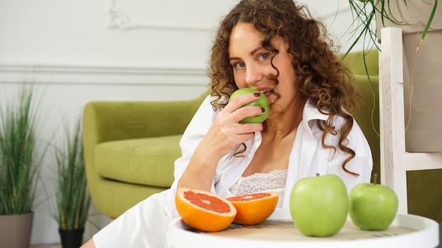 Mujer joven comiendo manzana verde en casa