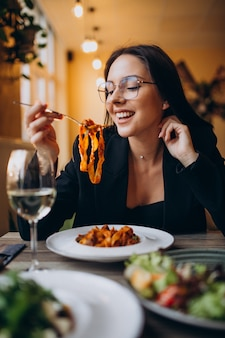 Mujer joven comiendo pasta en un café